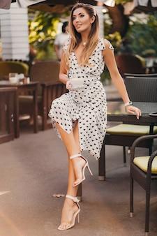 Seksowna piękna kobieta ubrana w białą drukowaną romantyczną sukienkę siedzi w kawiarni w słoneczny letni dzień