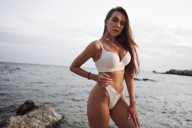 Seksowna piękna kobieta w białych strojach kąpielowych na wybrzeżu morza na zachód słońca