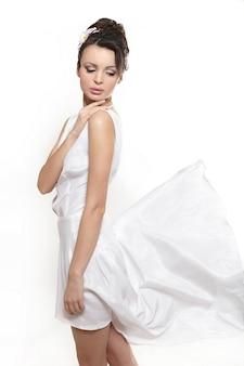 Seksowna piękna kobiety dama jest ubranym białą latanie sukni panny młodej odizolowywającej na bielu