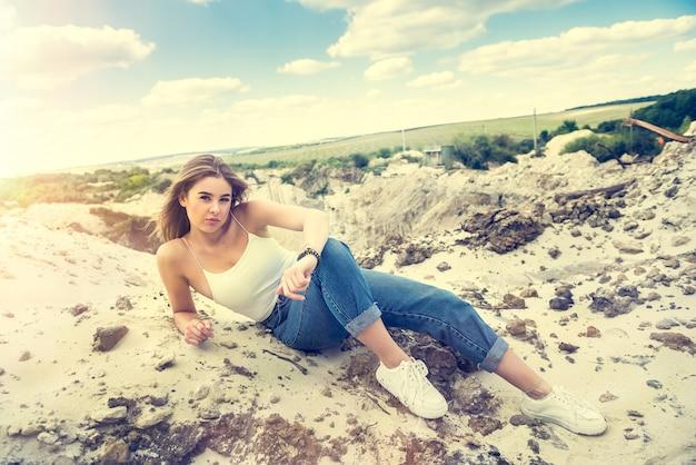 Seksowna piękna młoda kobieta pozuje dorywczo ubrania na kamieniołom piasku. na wolnym powietrzu