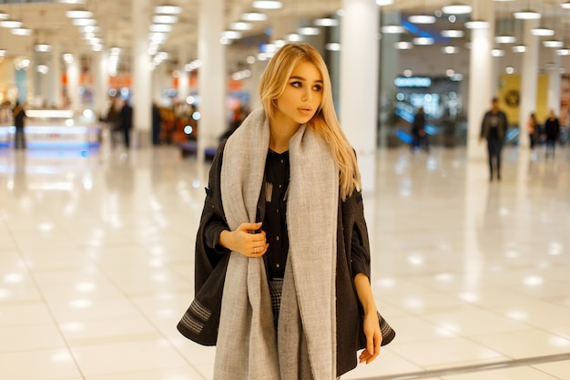 Seksowna piękna młoda kobieta w modny stylowy płaszcz w szarym szaliku pozowanie w centrum handlowym