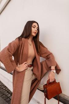 Seksowna piękna modna kobieta w modnym płaszczu ze skórzaną torebką pozuje pod ścianą w mieście