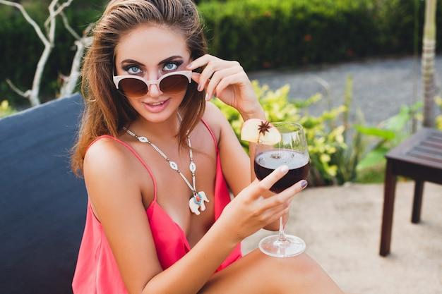 Seksowna stylowa kobieta w stroju strony mody na letnie wakacje przy lampce koktajlu, zabawy na basenie