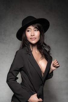 Seksowna szczupła brunetka kobieta ubrana w modny czarny garnitur bez stanika i czarny kapelusz jest sexy moda pozowanie studio strzał na białym tle na szarym tle.