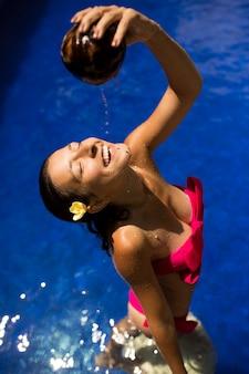 Seksowna szczupła brunetki młoda kobieta podlewania się świeżym mlekiem kokosowym w basenie z krystalicznie niebieską wodą. royal tropikalny ośrodek relaks.