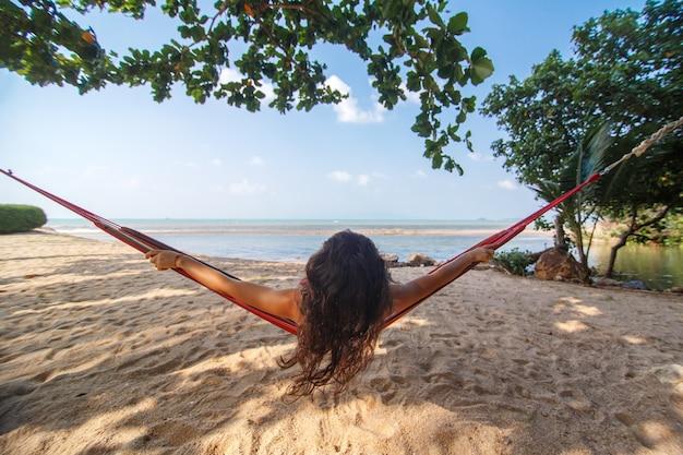 Seksowna szczupła dziewczyna lubi relaksować się w hamaku na wybrzeżu wyspy tropikalnego raju.