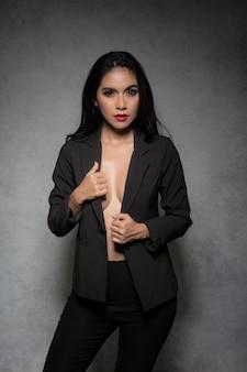 Seksowna szczupła kobieta ubrana w modny czarny garnitur bez stanika to seksowna, ciemna moda pozująca na szarej powierzchni