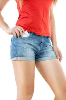 Seksowna szczupła kobieta w dżinsowych szortach pozuje z zapakowaną prezerwatywą