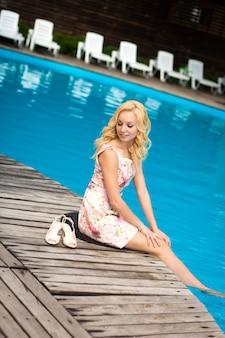 Seksowna szczupła, wspaniała młoda blondynka odpoczywa przy basenie w luksusowym hotelu