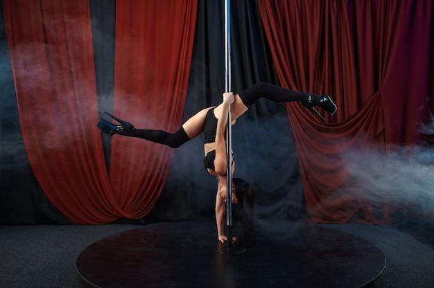 Seksowna tancerka w czarnej bieliźnie, taniec na rurze, tancerka striptizu. atrakcyjna striptizerka, taniec na kolanach, występy na rurze, gorąca dziewczyna tańczy
