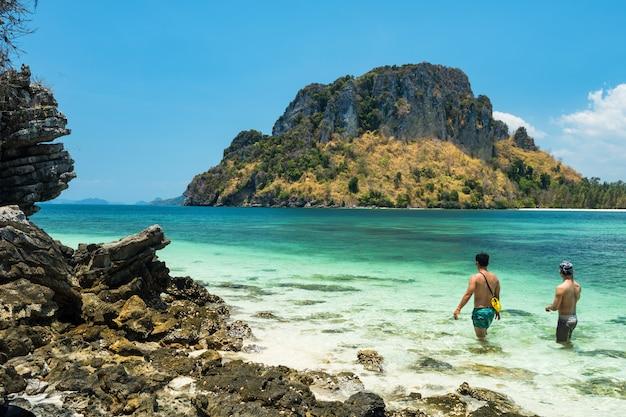 Seksowna, umięśniona para gejów lgbt spaceruje po krystalicznie turkusowym morzu na wyspie thale waek, niewidocznym krabi podczas letnich wakacji na południu tajlandii.