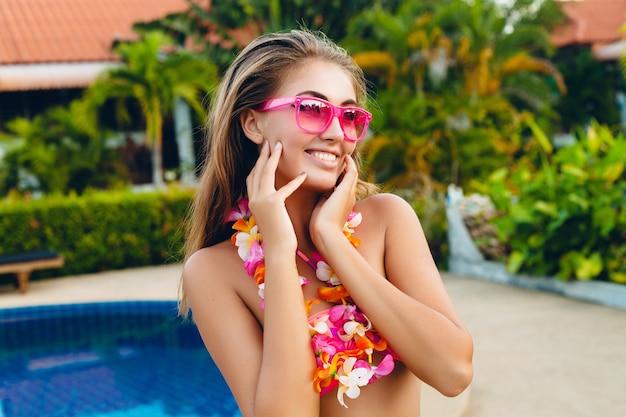 Seksowna uśmiechnięta kobieta na wakacjach bawiąca się na basenie w bikini i różowe okulary przeciwsłoneczne, tropikalne kwiaty na hawajach, kolorowy letni styl mody