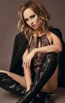 Seksowna uwodzicielska blondynka w bieliźnie i czarnym płaszczu