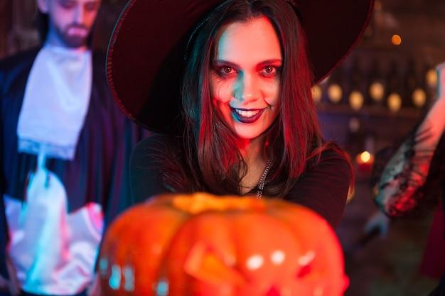 Seksowna wiedźma trzymająca magiczną dynię z przerażającym wyrazem na przyjęcie z okazji halloween. przerażająca czarownica.