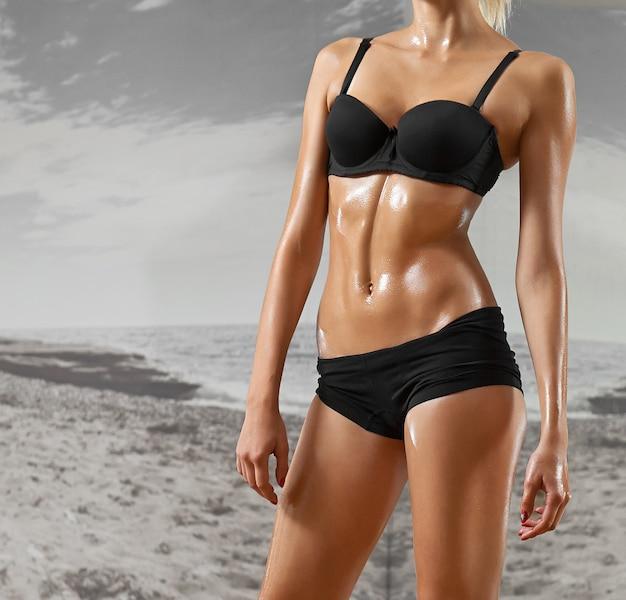 Seksowna, wysportowana, blondynka na siłowni, na tle lustra. sport, odzież sportowa, zdrowie, piękne ciało, patrzenie w kamerę, części ciała