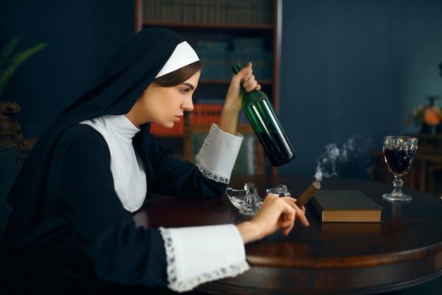 Seksowna zakonnica w sutannie pali cygaro i pije wino, okrutne żądze. zepsuta siostra w klasztorze, religia i wiara, grzeszni ludzie religijni, atrakcyjny grzesznik