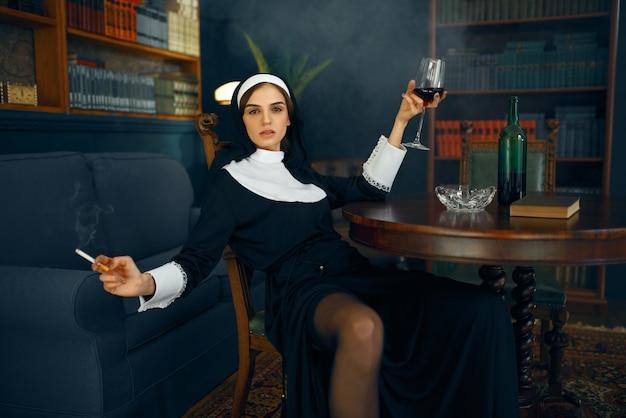 Seksowna zakonnica w sutannie siedząca w zdeprawowanej pozie z papierosem i kieliszkiem wina, okrutne pragnienia. zepsuta siostra w klasztorze, religia i wiara, grzeszni ludzie religijni, atrakcyjny grzesznik