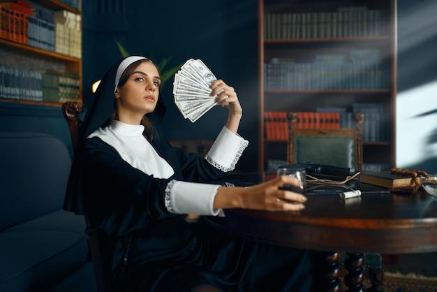 Seksowna zakonnica w sutannie trzymająca wachlarz dolarów i pijąca wino, okrutne żądze. zepsuta siostra w klasztorze, religia i wiara, grzeszni ludzie religijni, atrakcyjny grzesznik