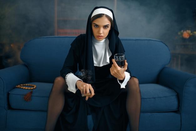 Seksowna zakonnica w sutannie z cygarem i lampką wina siedzi rozkładając nogi