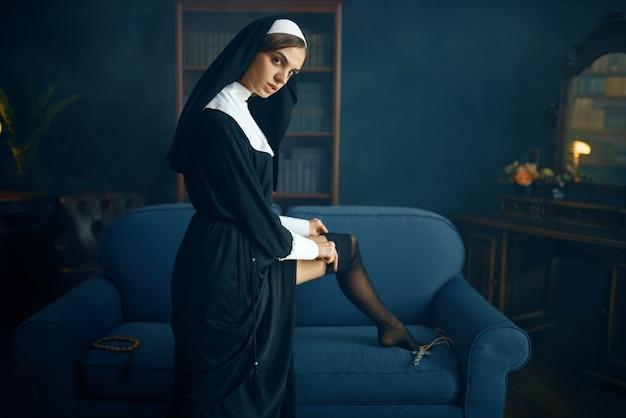 Seksowna zakonnica w sutannie zakłada pończochy z koronką, złośliwe żądze. do
