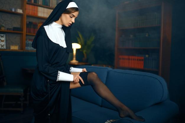 Seksowna zakonnica w sutannie zakłada pończochy z koronką, złośliwe żądze. zepsuta siostra w klasztorze, grzeszni ludzie religijni, atrakcyjna grzesznica