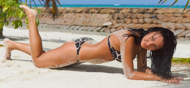 Seksowna, zgrabna dama wsparta na łokciach na plaży w bikini opalająca się w tropikalnym letnim słońcu