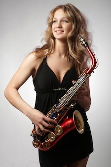 Seksowne atrakcyjne blondynki kobiety z saksofonem