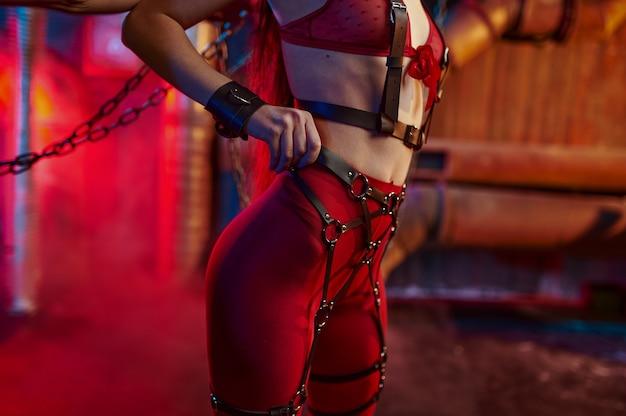 Seksowne ciało kobiety w czerwonym kostiumie bdsm przykuty łańcuchem, wnętrze opuszczonej fabryki. młoda dziewczyna w erotycznej bieliźnie, fetysz seksu, fantazje seksualne