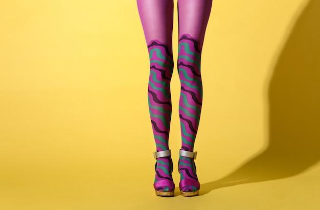 Seksowne kobiece nogi we wzorzyste fioletowe obroże lub rajstopy i buty na wysokim obcasie z klamrą