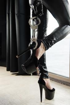 Seksowne kobiece stopy na wysokich obcasach i kajdankach