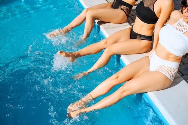Seksowne kobiety moczą stopy w basenie w ośrodku. piękne dziewczyny relaksują się przy basenie w słoneczny dzień, letnie wakacje atrakcyjnych dziewczyngirlfriend