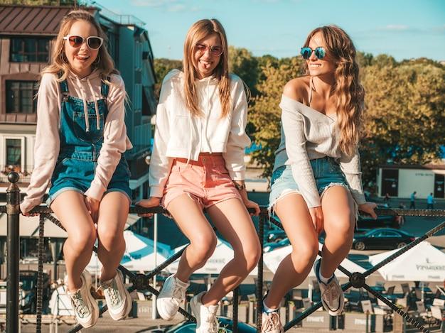 Seksowne kobiety siedzące na poręczy na ulicy. pozytywne modele zabawy w okularach przeciwsłonecznych. komunikują się i dyskutują