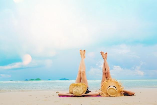 Seksowne kobiety swobodnie wypoczywają na plaży, ciesząc się ciepłym światłem