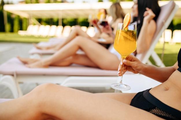 Seksowne kobiety ze świeżymi koktajlami odpoczywają na leżakach przy basenie. piękne dziewczyny relaksują się przy basenie w słoneczny dzień, letnie wakacje atrakcyjnych dziewczyn