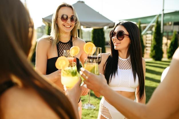 Seksowne kobiety ze świeżymi koktajlami odpoczywają przy basenie na świeżym powietrzu. piękne dziewczyny relaksują się przy basenie w słoneczny dzień, letnie wakacje atrakcyjnych dziewczyn