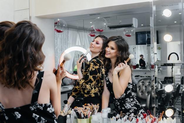 Seksowne młode dziewczyny bawią się i umalają na imprezę przed lustrem. moda i uroda.