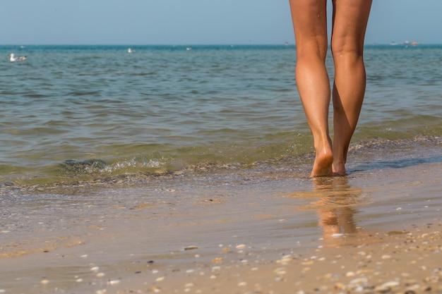 Seksowne nogi na plaży. chodzące kobiece stopy