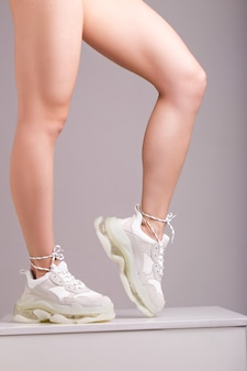 Seksowne nogi w białych tenisówkach
