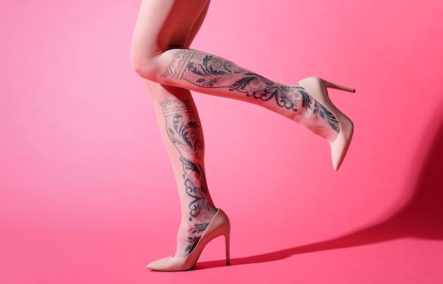Seksowne smukłe nogi młodej kobiety w różowym kołnierzu z ozdobnym kwiatowym wzorem