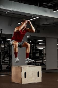 Seksowni muskularni mężczyźni korzystający z platformy na nogi na ciemnym kolorowym tle siłowni.