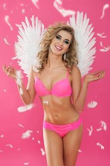 Seksowny anioł cieszący się spadającymi piórami