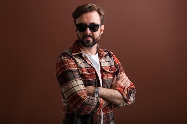 Seksowny atrakcyjny mężczyzna, pewny siebie hipster przystojny stylowy brodaty mężczyzna na brązowym