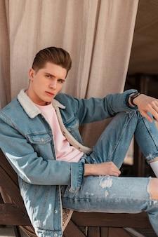 Seksowny atrakcyjny młody człowiek w modnej kurtce dżinsowej w vintage t-shirt w modnych dżinsach lubi relaks na świeżym powietrzu. przystojny seksowny facet w dżinsach ubrania na ulicy. codzienny wygląd młodości. zwyczajny styl.