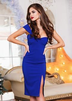 Seksowny biały model w eleganckiej niebieskiej sukience pozuje w luksusowym wnętrzu w studio