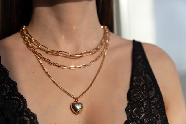 Seksowny dekolt z wieloma nowoczesnymi złotymi łańcuszkami z zawieszką w kształcie serca na modelce brunetki z długimi włosami