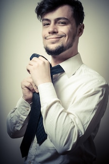 Seksowny elegancki biznesmen przystosowywa krawat