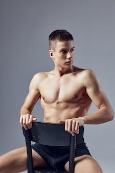 Seksowny facet z mięśniami siedzi na krześle