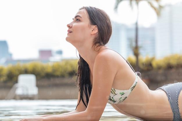 Seksowny kaukaski atrakcyjna kobieta model nosić bikini w deszczu.