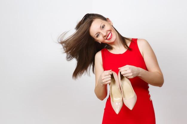 Seksowny kaukaski modny młody uśmiechający się z latające włosy kobieta w czerwonej sukience trzymając parę beżowych butów z czerwoną podeszwą jej zakupów na białym tle. skopiuj miejsce na reklamę.