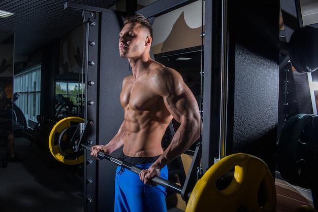 Seksowny mężczyzna na siłowni z hantlami. wysportowany mężczyzna z dużymi mięśniami i szerokimi plecami trenuje na siłowni, fitness i napompowanej wyciskaniu brzucha. rosja, swierdłowsk, 2 czerwca 2018 r.